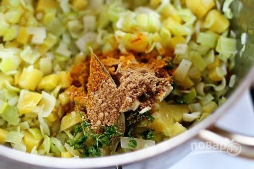 Добавьте мелко нашинкованный имбирь, карри, чеснок, петрушку и лавровый лист. Обжаривайте 2 минуты.
