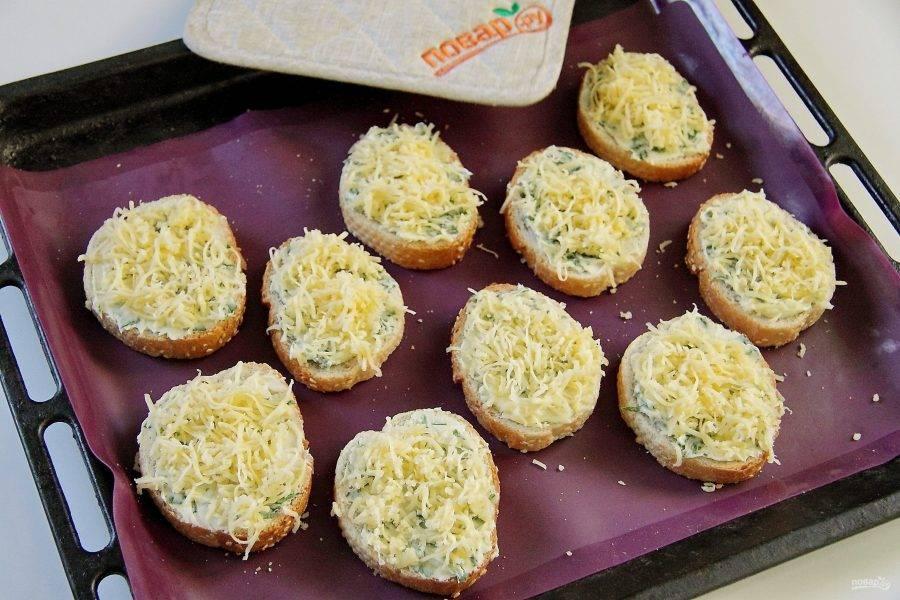 Ломтики батона намажьте ароматным маслом и выложите на противень. Сверху посыпьте тертым сыром.