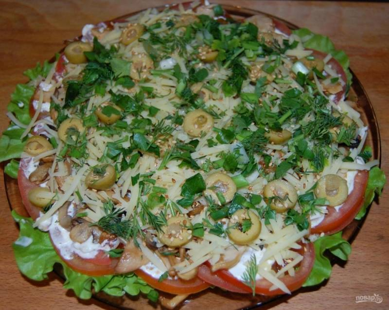8.Оливки нарезаю колечками и выкладываю поверх сыра. Мою и измельчаю зелень, посыпаю ею салат. Блюдо можно сразу подавать к столу.