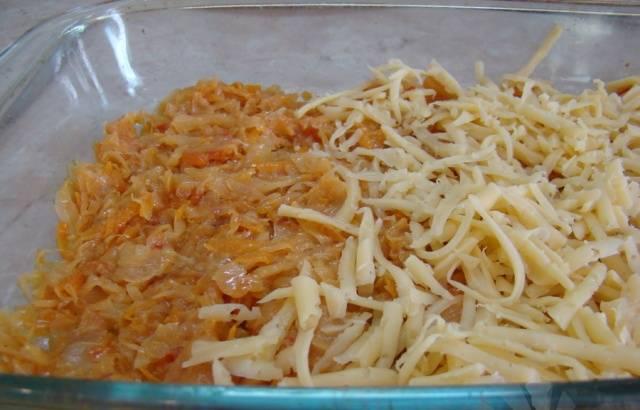 Смазываем форму для запекания маслом и выкладываем в нее половину подготовленной капусты. Сыр натираем на терке и посыпаем им капусту.