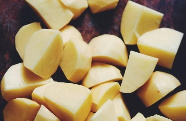 1. Картошку моем, чистим и режем кусочками среднего размера. Отвариваем и остужаем. Выкладываем в блюдо для запекания, посыпаем солью и специями.