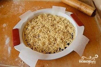 Натрите вторую часть теста на крупной тёрке. Посыпьте им пирог. Отправьте на 25 минут в духовой шкаф.