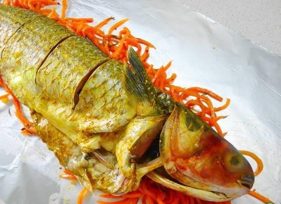 Сверху на морковь укладываем рыбину, и делаем надрезы.