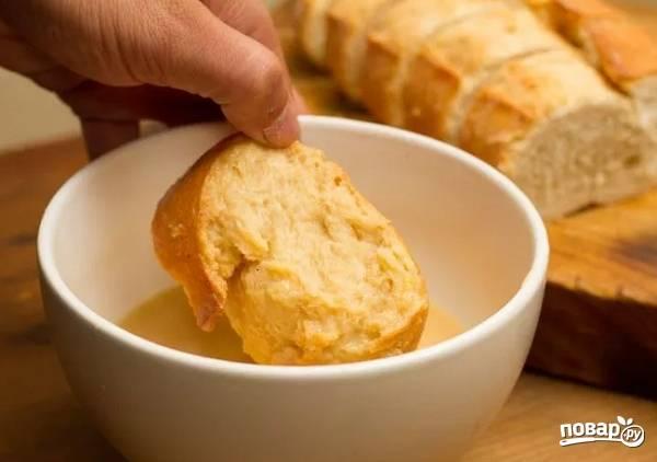 7. На сковороде разогрейте немного сливочного масла. Каждый ломтик окунайте в яичную смесь со всех сторон.