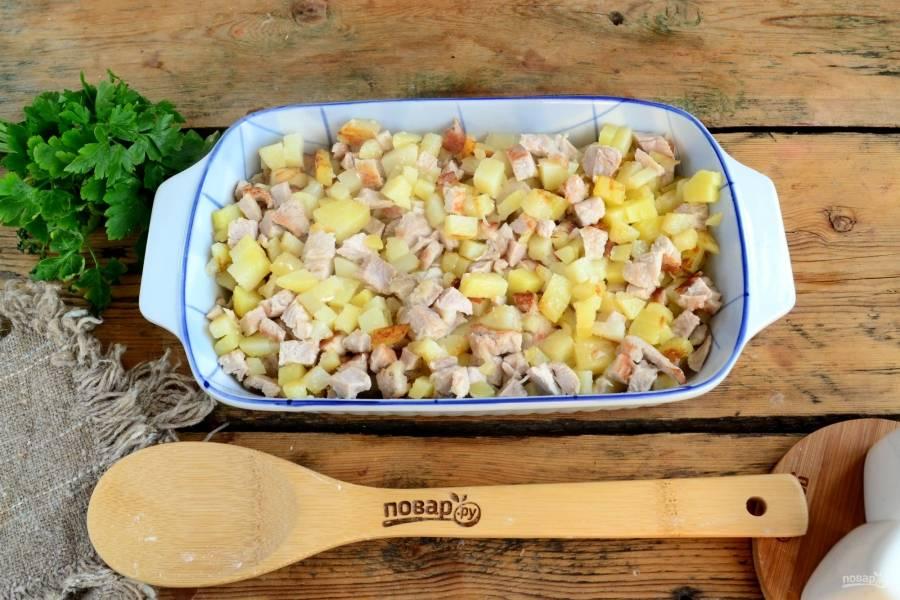 Выложите обжаренный картофель и индейку в жаропрочную форму для запекания.