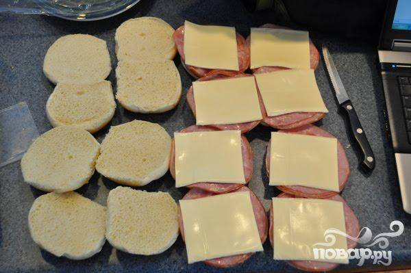 2.Булочки разрезать пополам, их внутреннюю часть смазать майонезом (при желании). Сложить ломтик ветчины так, чтобы он не сильно выглядывал из булочки, на ветчину уложить ломтик сыра. Накрыть булочку верхушкой.