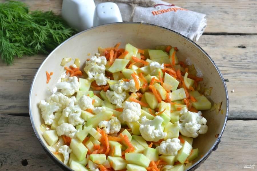 В сковороду налейте растительное масло. Поставьте на огонь, чтобы оно хорошо прогрелось. В разогретую сковороду высыпьте лук, поджарьте его до прозрачного цвета. Затем добавьте морковь, пару минут пассеруйте. Последними добавьте соцветия капусты и брусочки кабачка. Накройте крышкой, тушите на медленном огне до готовности, периодически перемешивая.