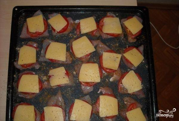Сыр нарежьте ломтиками. Выложите его поверх помидоров. Поставьте противень с курицей в духовку. Запекайте примерно 20-25 минут.