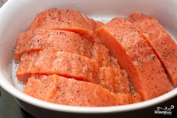 Филе лосося нарезаем порционными кусочками шириной примерно в 5-6 см. Кладем в глубокую форму для запекания. Солим, перчим, сбрызгиваем лимонным соком.