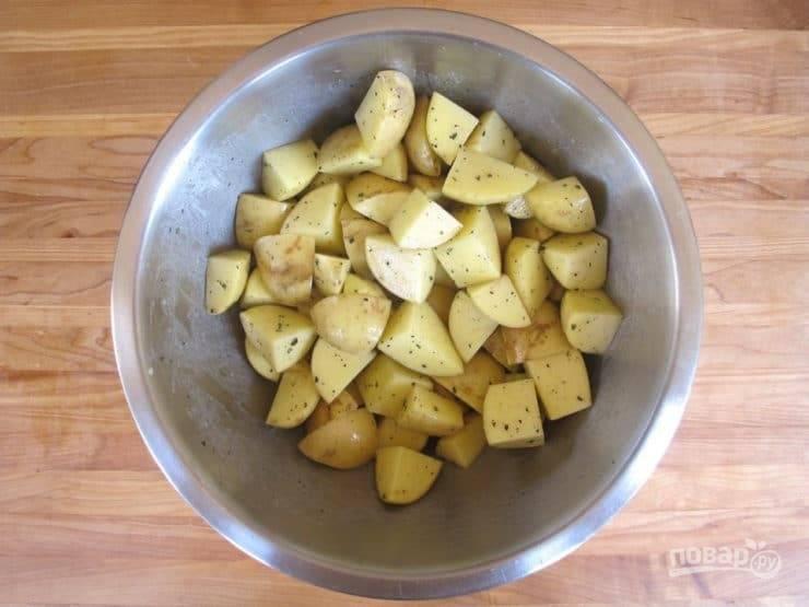 2. Картофель почистите и нарежьте крупными кубиками. Затем смешайте с измельчённым розмарином и очищенным чесноком. Добавьте масло, соль и перец.