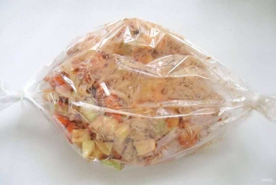 Выложите овощи с курицей в рукав для запекания. Отправьте его в духовку.