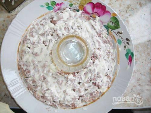4. Выкладывайте кубики мяса поверх картофеля и смажьте майонезом.
