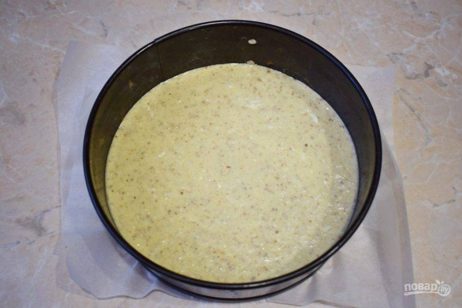 Подготовьте форму для пирога. Лучше всего взять разъемную форму и дно застелить бумагой для выпечки. Перелейте готовое тесто в форму.