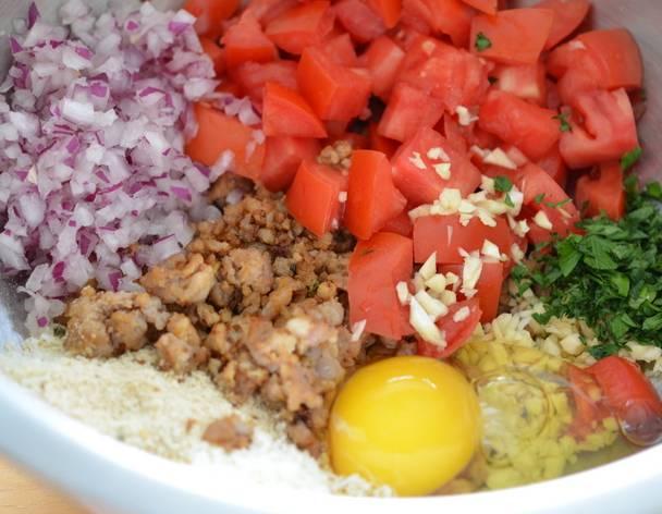 2. Для начинки смешаем обжаренные грибы, измельченные помидор, лук, чеснок. Панировочные сухари, яйцо и специи всыпаем чуть позже. Я добавляла еще зелень, так как начинка получилась жидковатой.