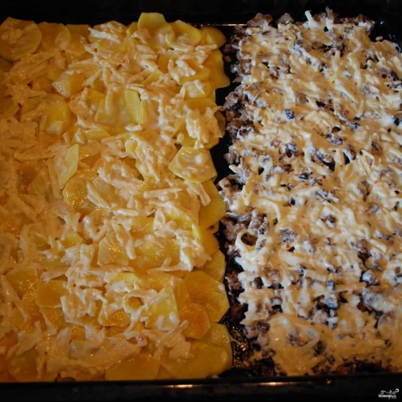 Сыр натрите на терке, смешайте с майонезом и сметаной. Равномерно нанесите сырную массу на картошку и грибы.