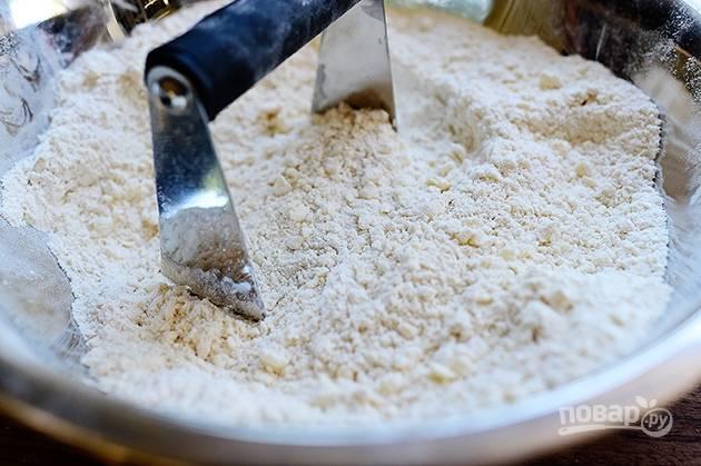 2. Добавьте кубики сливочного масла и перемешайте тесто, оно будет иметь рассыпчатый вид.
