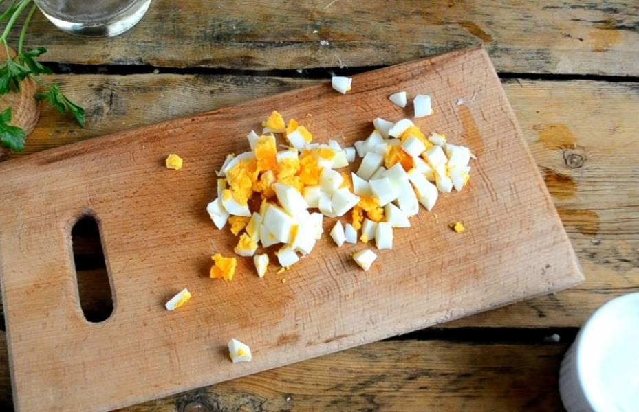 Яйца отварите вкрутую и порежьте на мелкие кусочки. Смешайте грибы, сыр и яйца.