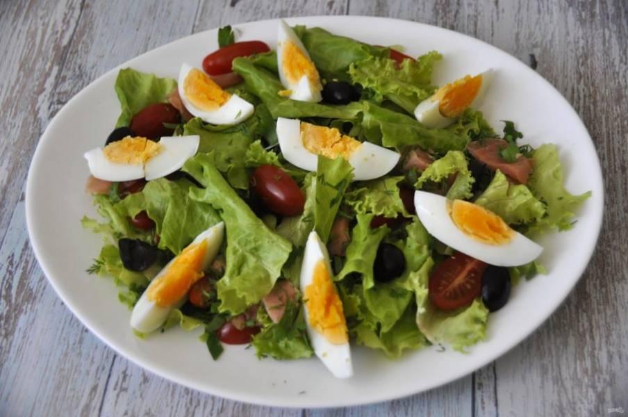 Добавьте маслины, сверху выложите дольки вареного яйца.