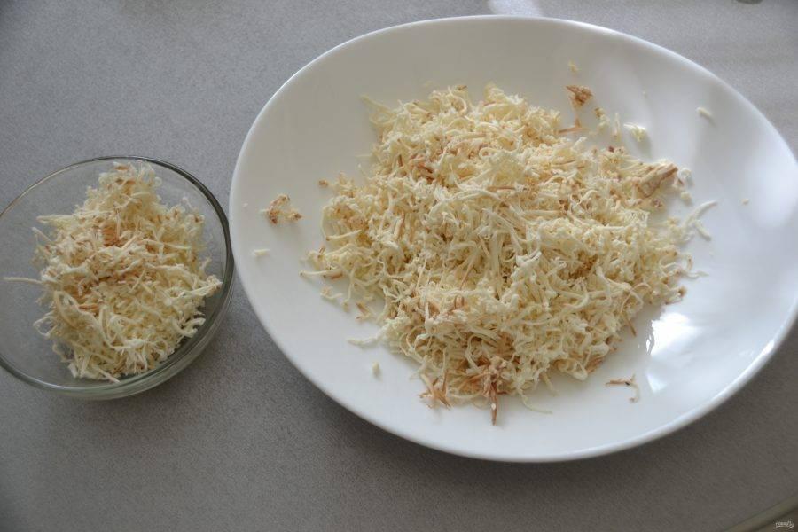 Натрите на терке копченый сыр, часть сыра отложите в отдельную тарелку.