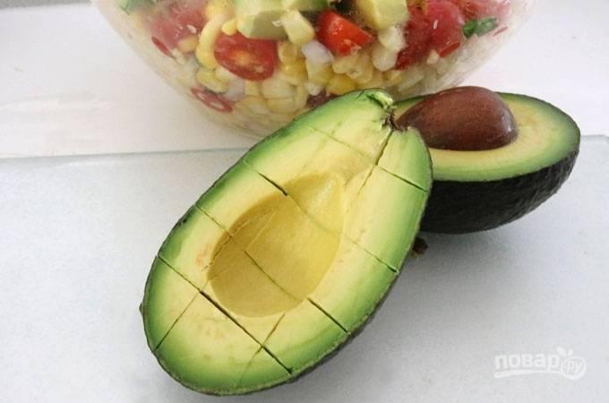 6. Авокадо разрежьте пополам, удалите косточку. Мякоть нарежьте кубиками и добавьте в салатник.