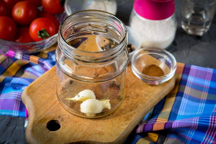 На дно стерилизованной банки выложите очищенные зубчики чеснока и перец горошком.