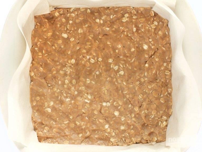 6.Застелите форму для выпечки пергаментом, выложите большую часть теста и разровняйте его в один слой.