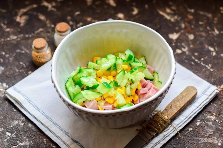Свежий огурец вымойте и просушите, обрежьте концы с обеих сторон. Нарежьте огурцы небольшими кубиками. Добавьте нарезку в салат.