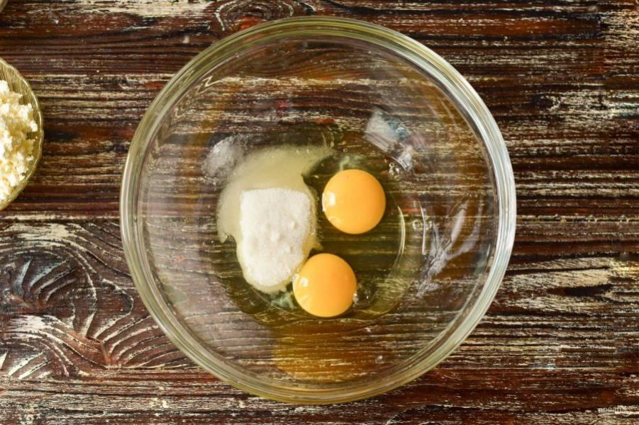 В миску вбейте куриные яйца. Всыпьте сахар.