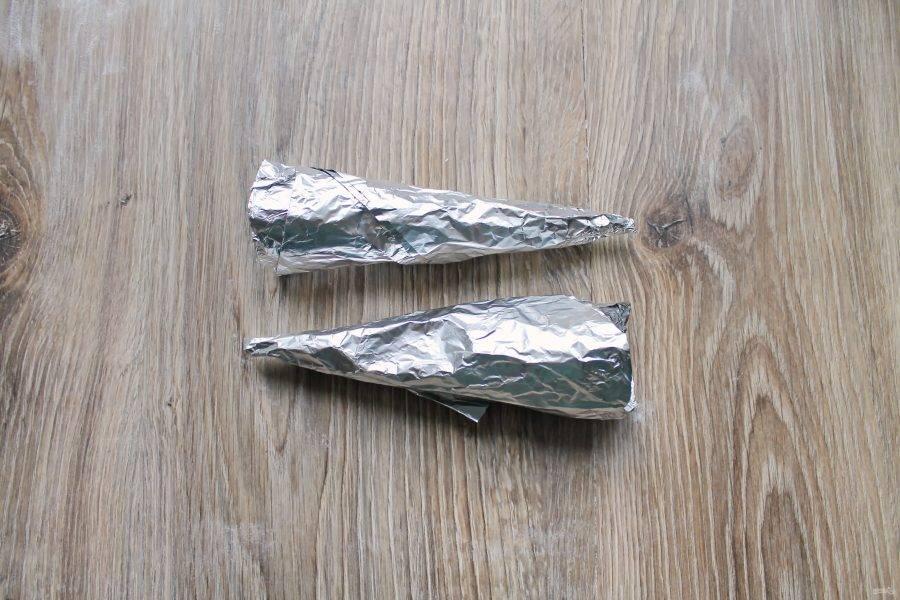 Если у вас нет специальных конусов, вполне можно сделать их из пищевой фольги. Сложите кусок фольги пополам, сделайте из него конус. Для жесткости забейте внутреннюю часть бумагой для выпечки.