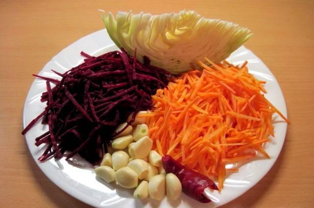 Капусту разрежем на небольшие куски, чеснок почистим и разделим на зубчики, на крупной терке натрем свеклу и морковь, острый перец очищаем от семян.