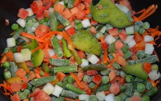 Добавляем тертую морковь и замороженные овощи.