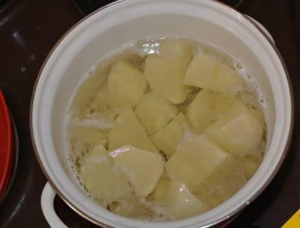 Дрожжевое тесто можно купить в кулинарии или сделать самому по любому рецепту. Ставим тесто в теплое место, пусть подходит. А пока займемся картошкой для начинки. Чистим картофель, разрезаем на несколько частей и ставим варить.
