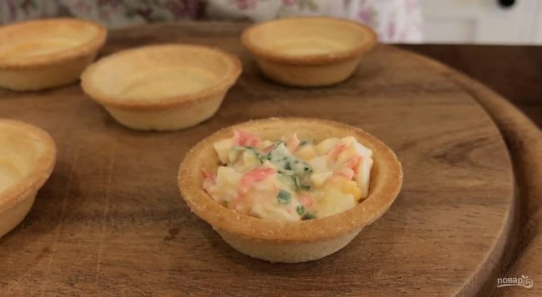 2. Переложите начинку в миску, добавьте немного майонеза, перемешайте. Тонкими пластинками нарежьте красную рыбу. Начинку аккуратно выложите в тарталетки.