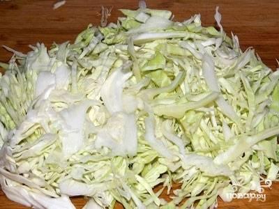 Затем добавляется главный ингредиент блюда - нашинкованная белая капуста. Всё обжаривается вместе на среднем огне. Не забываем помешивать.
