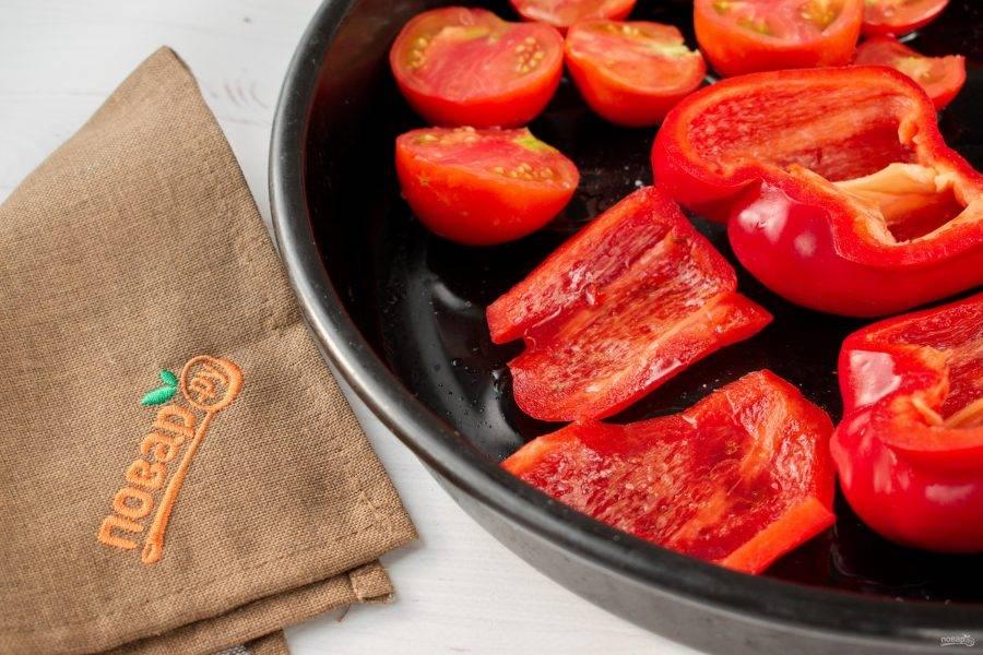 Помидоры и перец разрежьте на половинки, у перца удалите семена. Полейте оливковым маслом, посолите и поперчите. Поставьте в духовку запекаться на 40 минут при 200 градусах.