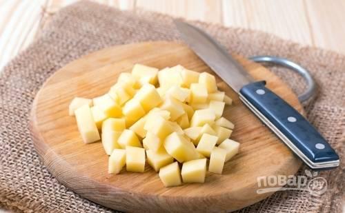 Картофель очистите, промойте и нарежьте мелкими кубиками.