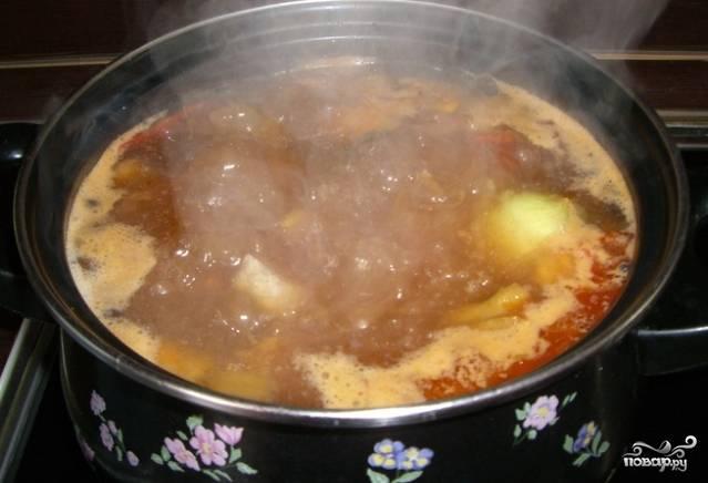 4. Очищенный картофель разрежьте на кубики. Выложите в бульон. Дайте закипеть. Затем переложите в бульон с картошкой тушеную с овощами свинину. Варите на медленном огне, пока картошка не начнет развариваться. Посолите. Добавьте черный молотый и на кончике ножа красный жгучий перец.
