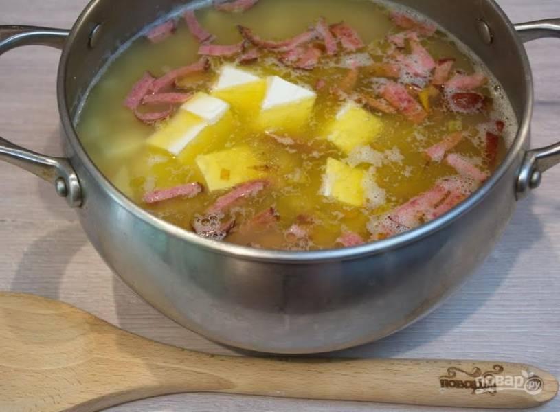 7. Спустя время добавьте в суп зажарку. Измельчите кубиком или натрите на терке плавленый сырок. Добавьте его в суп. Помешивая хорошо прокипятите суп. При кипении сырок разойдется, создаст неповторимый вкус, изменит цвет супа на молочный, придаст сливочные нотки.