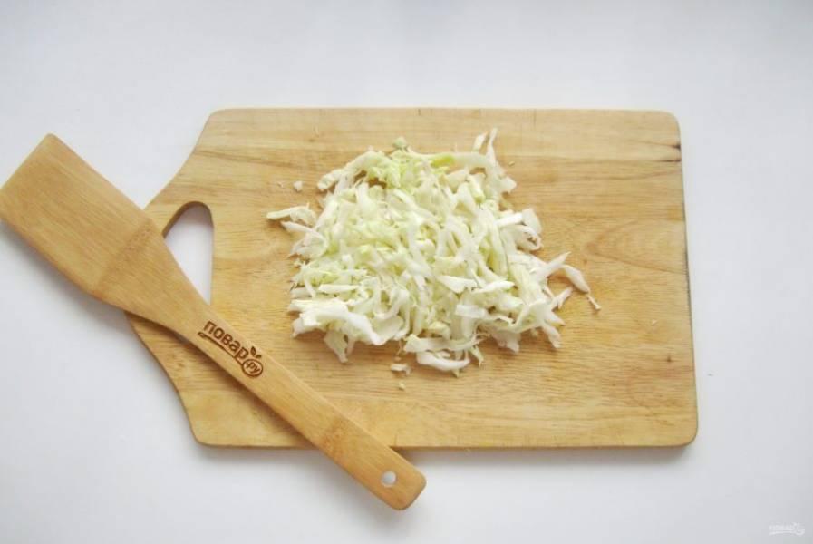 Капусту нарежьте тонкой соломкой. Немного посолите и помните руками, чтобы она стала мягче. При желании можно добавить немного лимонного сока.
