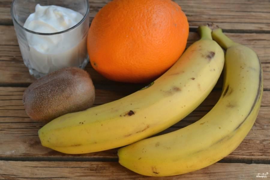 Подготовьте фрукты. Бананы порубите кубиками, киви порежьте на пластины, а дольки апельсина нарежьте кубиками. Также приготовьте крем: смешайте сметану с сахаром, взбейте её миксером до загустения. Можно добавить 1 ст. ложку загустителя для сметаны, если крем слишком жидкий.