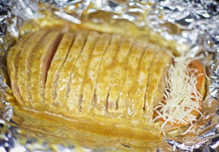6. Выкладывайте нарезанные чеснок и помидор между кусочками мяса, а сверху щедро посыпьте тертым сыром.