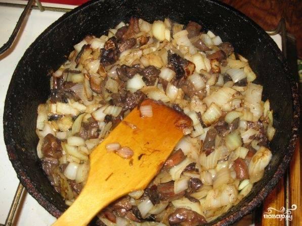 2. Луковицы очистить и нарезать кубиками. На сковороде хорошо разогреть растительное масло и отправить туда лук. Пока лук золотится, вымыть и нарезать небольшими кусочками грибы. Отправить к луку и жарить до готовности.