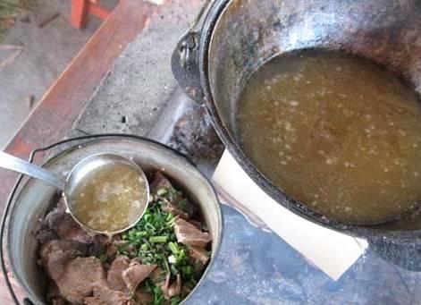Нарезанный лук перекладываем в кастрюлю, добавляем к нему мясо, часть свежей зелени, стебли чеснока, молотый перец и заливаем бульон так, чтобы он прикрывал содержимое кастрюли наполовину.