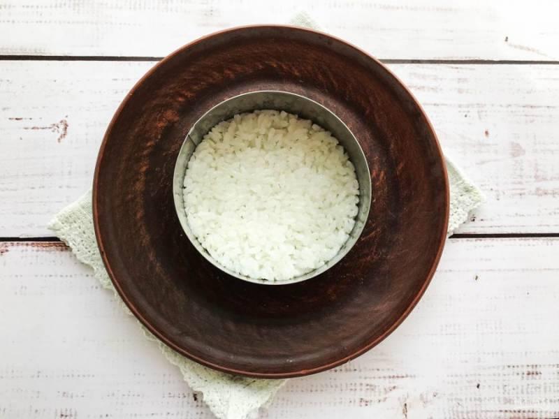 На тарелку выложите сервировочное кольцо. Нижний слой сделайте из риса. Рис смешайте с маслом печени трески.