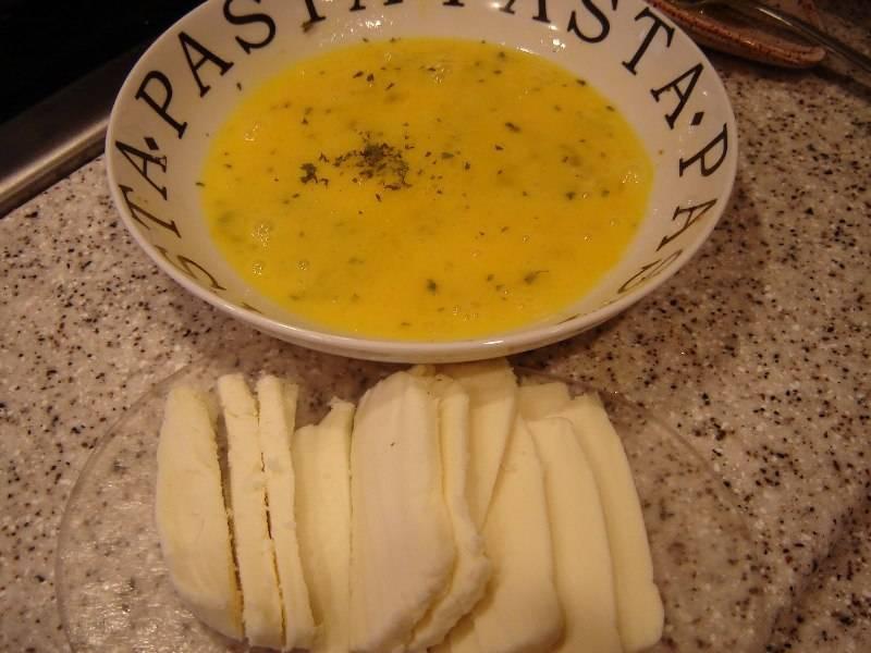 В миске с помощью вилки размешайте яйца, добавьте пропущенный через пресс чеснок, петрушку и щепотку соли. Окуните кусочки хлеба в яичную смесь, затем положите на один кусочек пластинку сыра и накройте вторым.