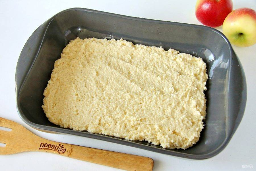 7. Форму для выпечки смажьте маслом. Выложите тесто и разровняйте его ложкой.