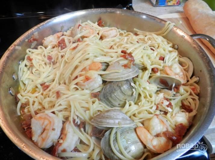 Отваренную пасту, слив воду, отправьте к морепродуктам, перемешайте и немного прогрейте.