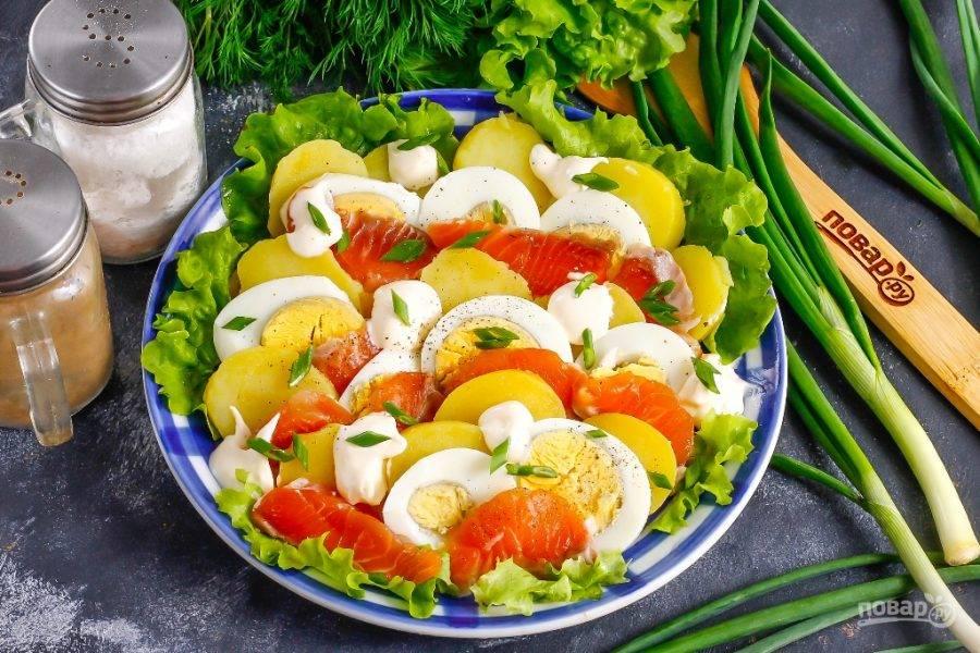 Посолите салат, поперчите. Промойте стебли зеленого лука и измельчите их. Выложите между нарезок майонез или сметану любой жирности, присыпьте сверху измельченным зеленым луком. По желанию можно использовать укроп, петрушку.