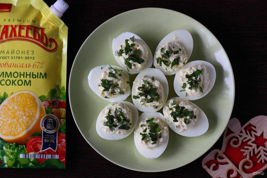Получившейся начинкой наполните половинки яиц, украсьте зеленью и можно подавать закуску к столу. Приятного аппетита!