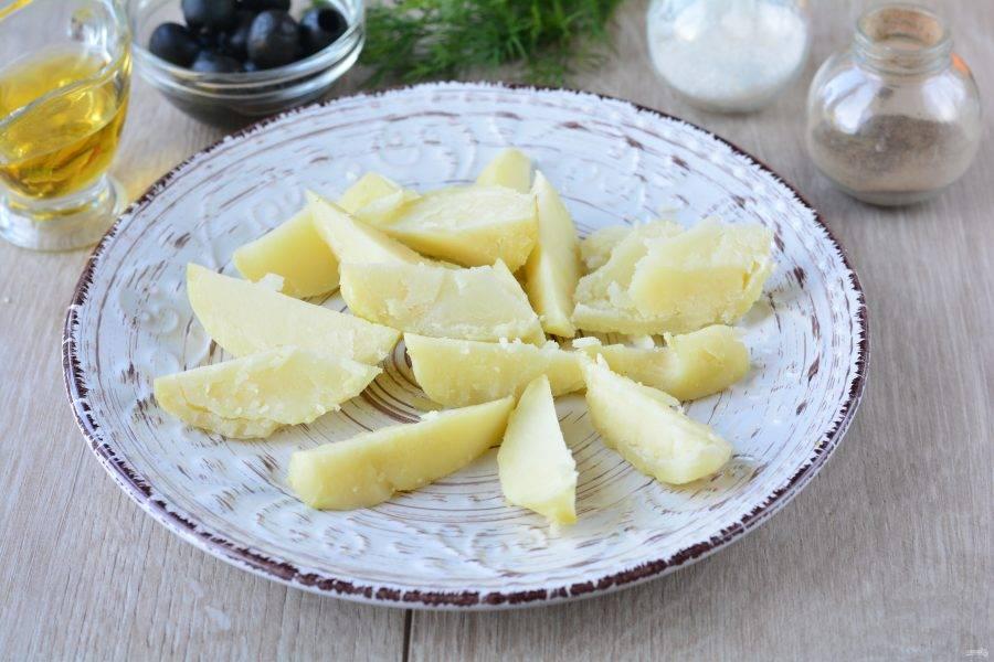 Сварите картофель до готовности в подсоленной воде, остудите и нарежьте дольками, выложите на блюдо.